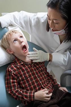 Boy getting teeth examined by Dentist