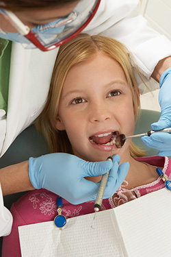 Girl at the Dentist getting teeth examined
